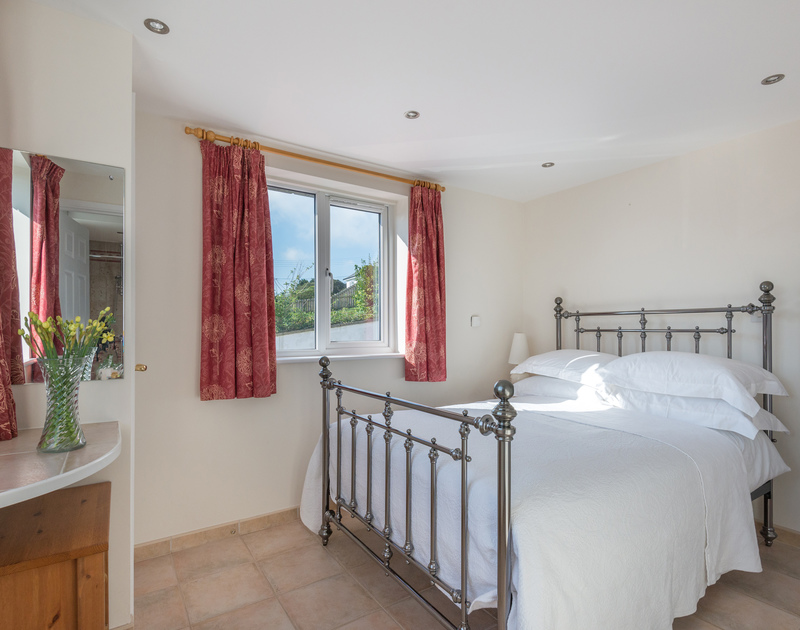 Polmorla's ground floor double bedroom has decorative bedsteads and an ensuite shower room