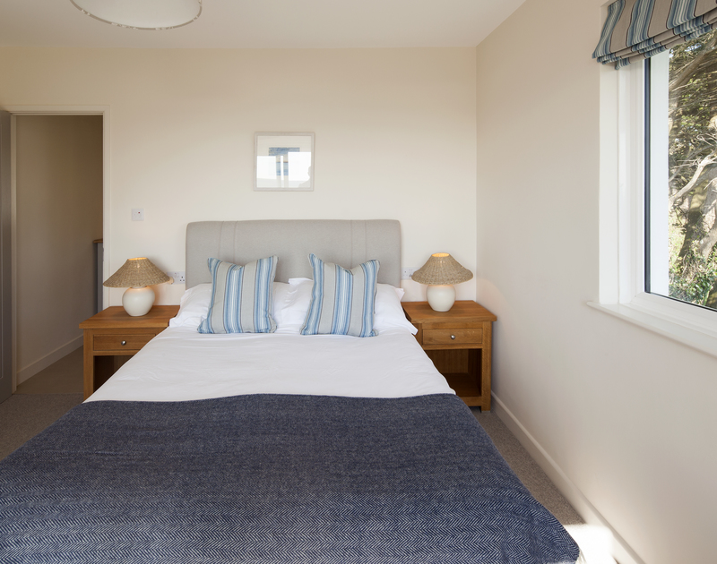 Smart king size double bedroom that opens onto a balcony with sea views and an ensuite shower room at Brae Heights.