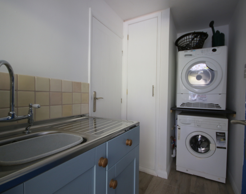 The compact, practical utility room of Slipway 21, with washing machine and sink