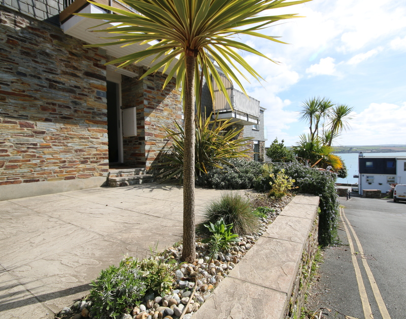 The tiled patio of Slipway 21, a holiday rental in Rock,  with its coastal plants and view of the estuary