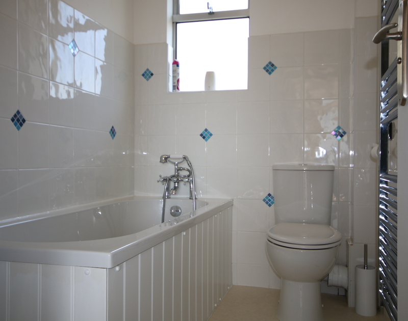 The glossy white and blue tiled bathroom at Slipway 21, selfcatering rental in Rock.