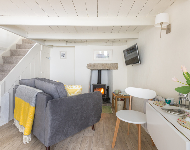Cosy up on the sofa by a roaring log burner at The Bakehouse, a self-catering cottage to rent in Port Isaac, North Cornwall