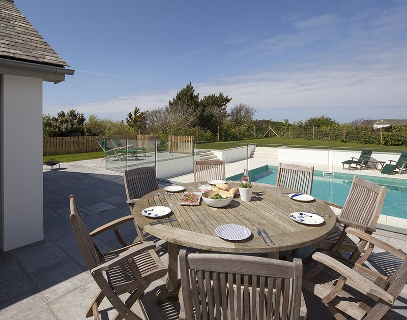The poolside terrace is the perfect place for enjoying meals on sunny Cornish days at Mordros, a self catering holiday house at Greenaway.