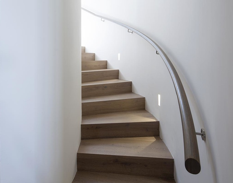The attractive curved wooden staircase up to the first floor at Mordros, a luxury holiday rental in Daymer Bay.