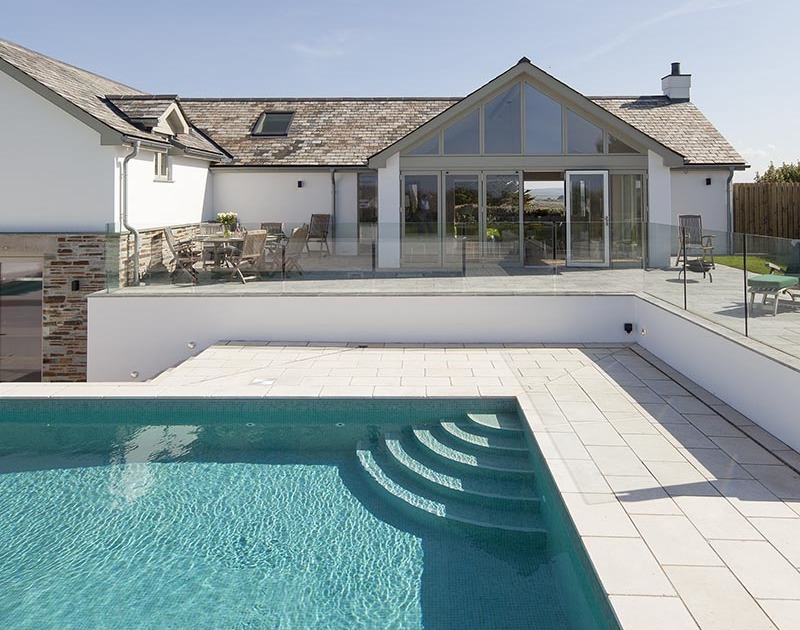 The inviting swimming pool with sunny terraces all around at the rear of Mordros.
