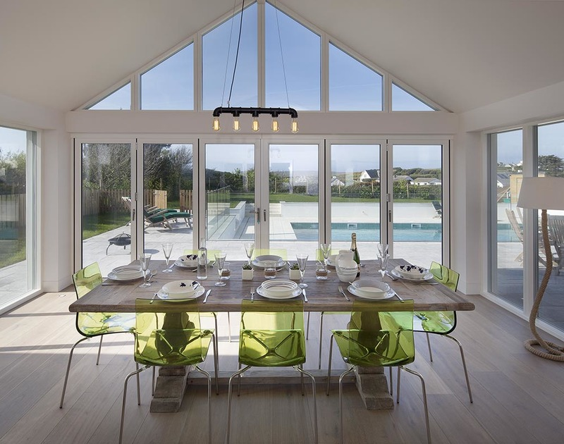 Enjoy family meals overlooking the garden and pool from the light filled dining area in Mordros a holiday house to rent above Daymer Bay.