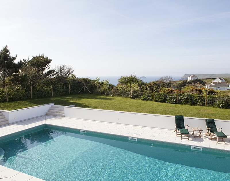 Stunning views of Pentire Point and Newlands Rock over the swimming pool and the surrounding garden at Mordros.