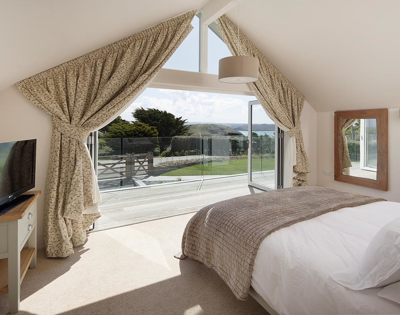 Lovely views of Brea Hill and the Camel Estuary through the bi-fold doors of the master bedroom suite at Mordros, Greenaway.