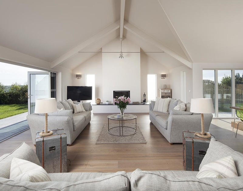 Three spacious sofas provide plenty of lounging space around the TV and open fire in the open plan living room at Mordros ideally placed between Greenaway and Daymer Bay in North Cornwall.