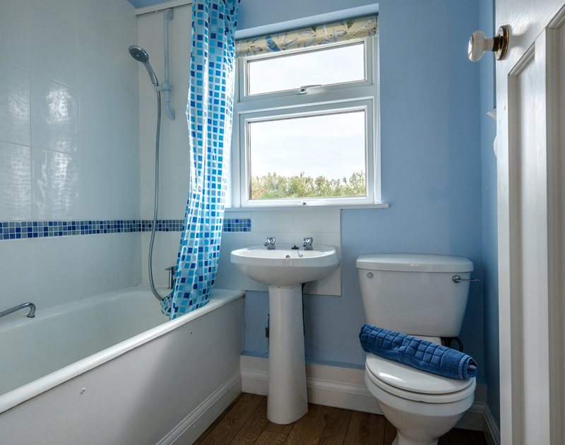 The ensuite bathroom at Tresawl with bath and overhead shower.