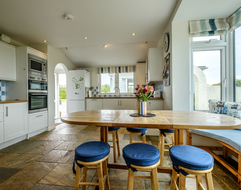 The practical kitchen in Tresawl with dining table and window seat.
