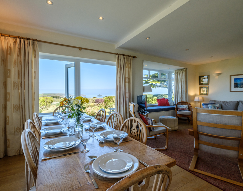 The good sized dining table with stunning far reaching country and sea views at Tresawl, set above Epphaven near Polzeath in Cornwall.