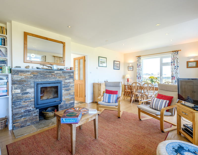 The light filled living room with dining table in Tresawl, a self catering holiday property set above the cove at Epphaven near Polzeath in Cornwall.