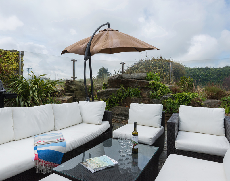 Enjoy drinks or meals on the sunken patio and rockery area at Penny Liggan where the Cornish breezes are kept at bay by the glass balcony completely enclosing it.