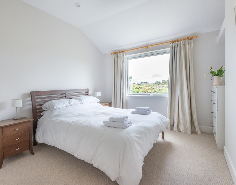 The good sized double bedroom with king size bed and rural views over St Enodoc Golf Course in Rock, North Cornwall.