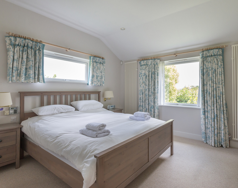 The master bedroom at Penny Liggan with a super king size bed and views of the well known St Enodoc Golf Course.