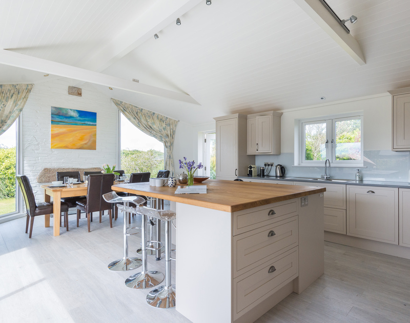 The useful kitchen island with breakfast bar in the light filled kitchen at Penny Liggan, a self catering holiday property a short walk away from the waterfront and beach in Rock, North Cornwall.