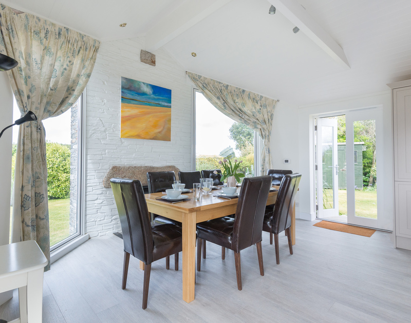 The dining room with large windows in the sociable, open plan kitchen/dining room at self catering Penny Liggan.
