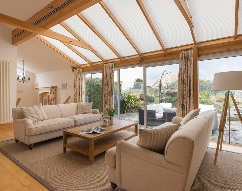 The natural light that fills the sitting room comes from the sliding doors to the patio and the wonderful glass ceiling above the sofas at Penny Liggan in Rock.