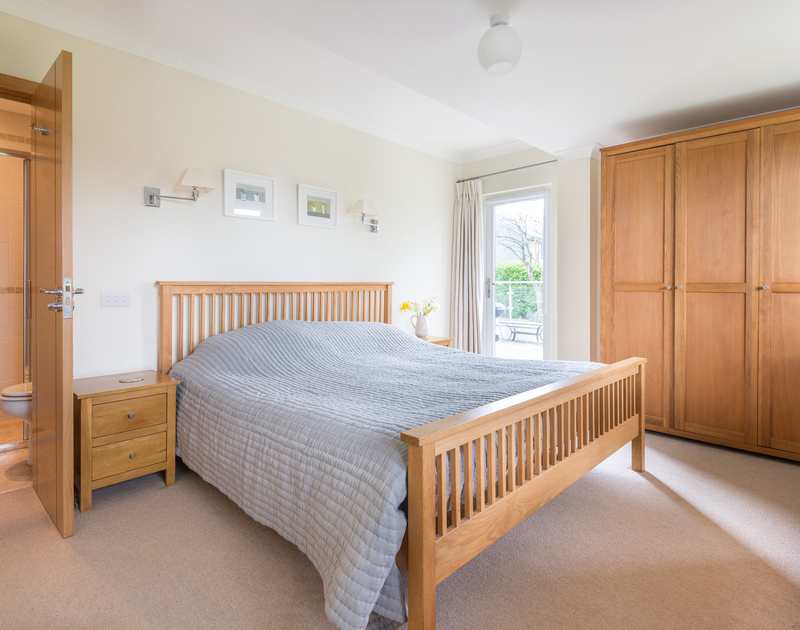 A double bedroom on the ground floor with private access to the sun terrace at Ragleighs, a luxury holiday house to rent above Daymer Bay in North Cornwall.