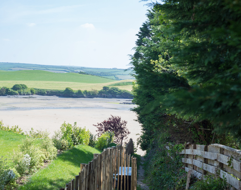 The path leading to the beach of Tregye, a luxury holiday house in Rock, Cornwall, with ample parking space and lawned garden.