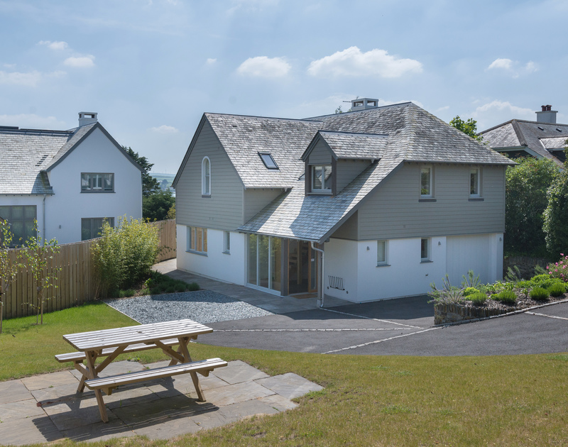 The exterior of Tregye, a luxury holiday house in Rock, Cornwall, with ample parking space and lawned garden.