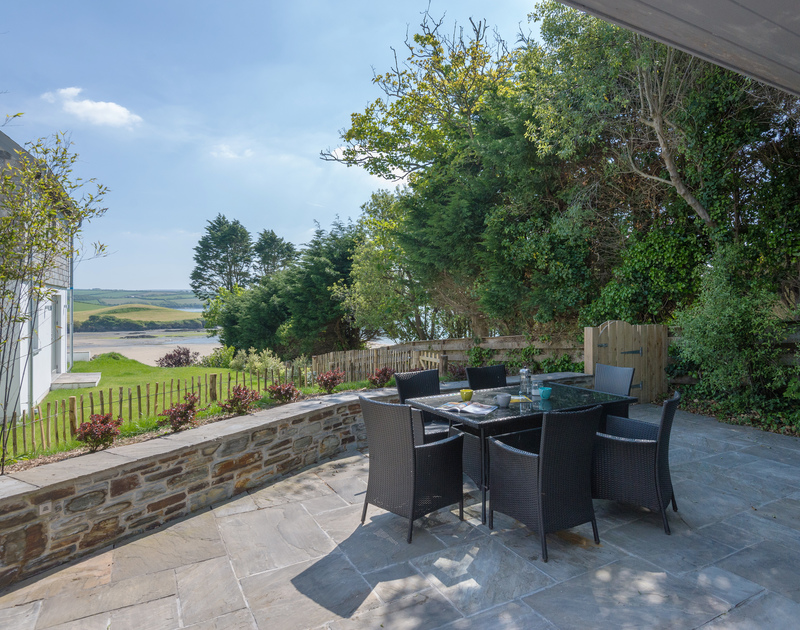 The sunny terrace eating area of Tregye, a luxury holiday house in Rock, Cornwall, with ample parking space and lawned garden.