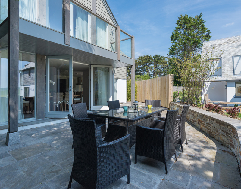 The view of the rea patio and eating area of the beach house at Porthilly, Tregye, a luxury holiday house in Rock, Cornwall, with ample parking space and lawned garden.