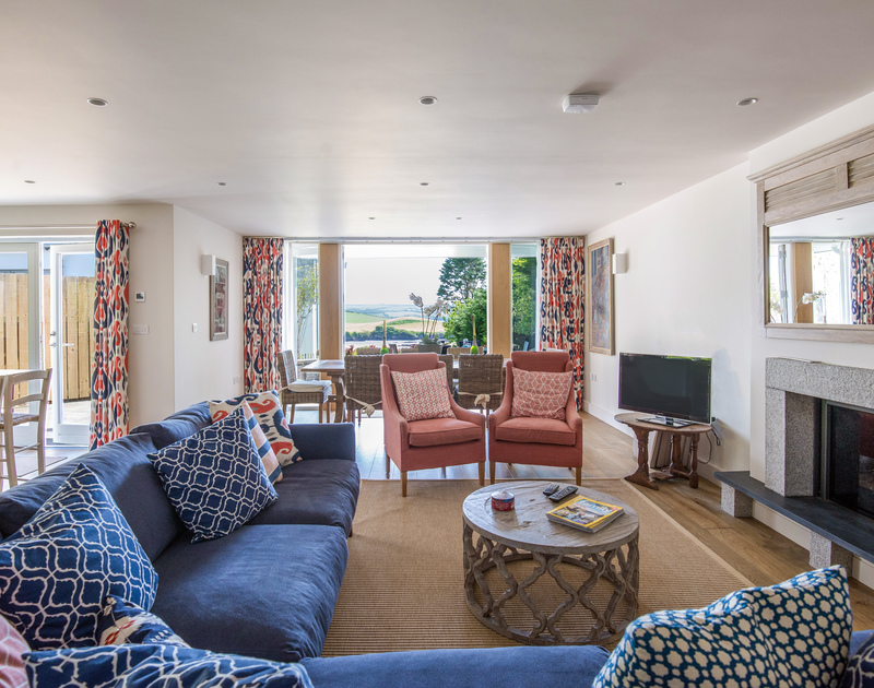The elegant, stylish sitting room of Tregye, a luxury holiday house in Rock, Cornwall, with corner sofa and two armchairs.