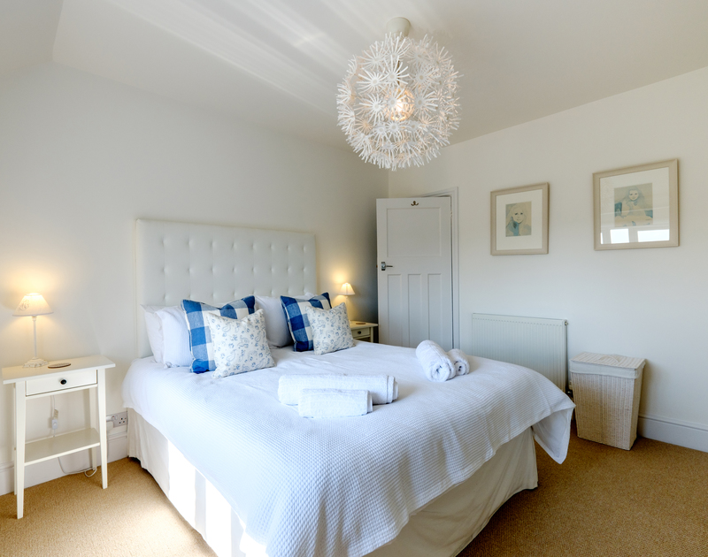 The soothing white master bedroom at The Moorings in Rock, Cornwall offers a luxurious sanctuary