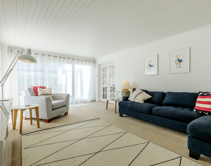 The large, spacious and light filled living room at The Moorings in Rock, a stylish and comfortable self catering holiday cottage