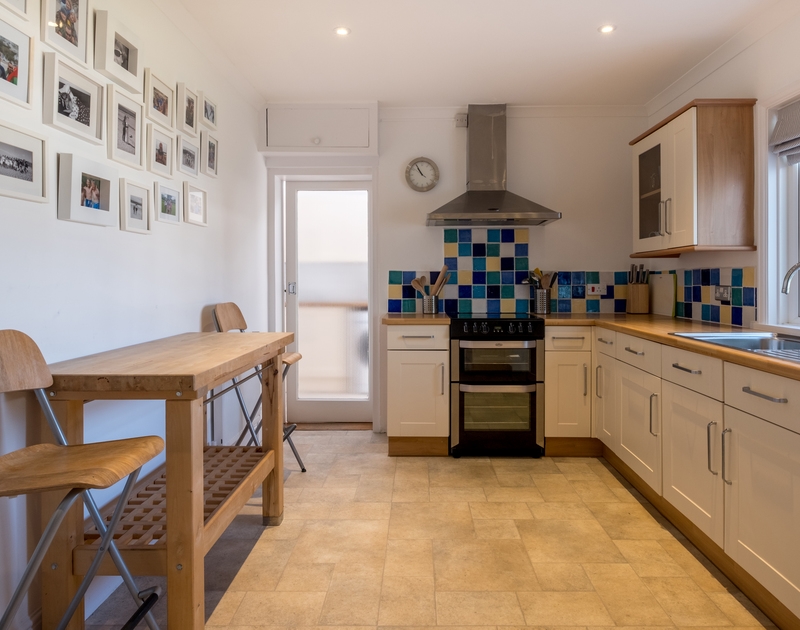 The well planned and light filled kitchen of The Moorings, a self-catering holiday rental in Rock, Cornwall, with adjacent utility room.