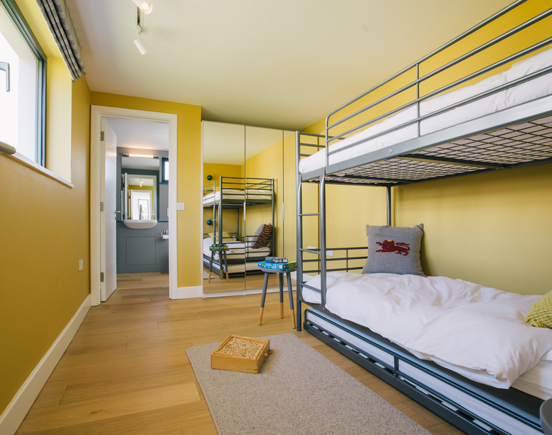 The second bedroom at White Star is a cheerful bright bunk room that can sleep two or three guests with an ensuite shower room