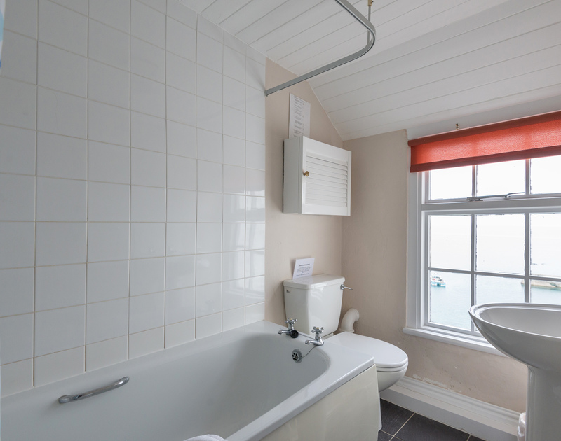 Bathroom with a view of Port Isaac's harbour at Northcliffe Garden Flat