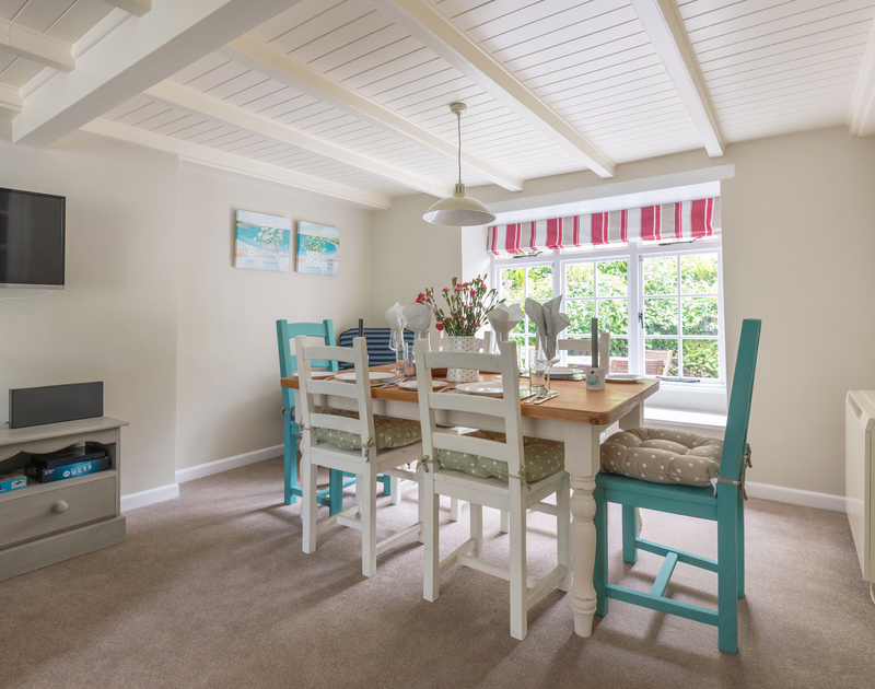 Poplar Cottage in Port Isaac has a colourful dining table that benefits from light flooding in from the pretty sash windows on either side of the open plan lining and dining room on the ground floor.