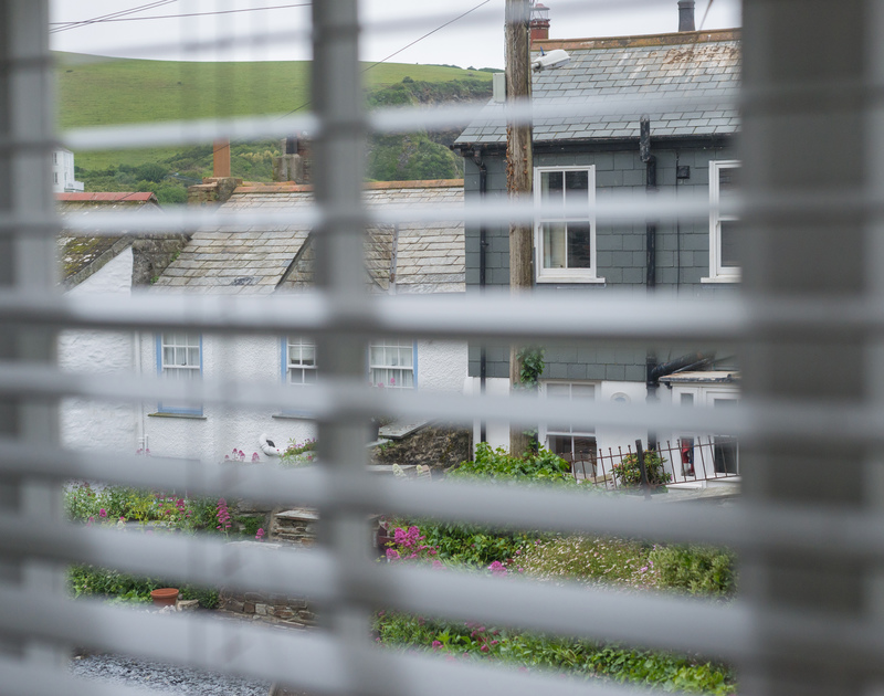 A glimpse through the blinds from the double bedroom to the fisherman's cottages opposite Poplar in Port Isaac on the North Cornish Coast.