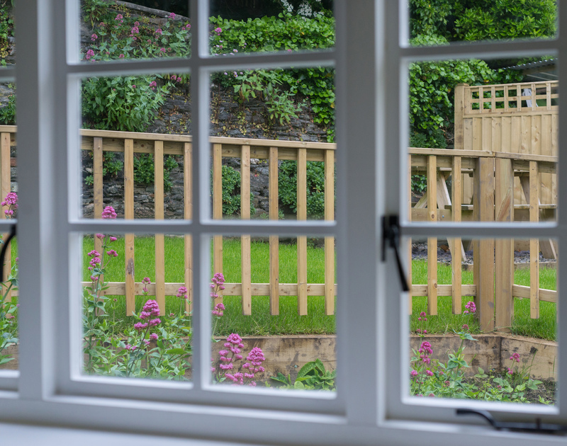 The single bedroom at Poplar, a self catering holiday house in Port Isaac,enjoys garden views through the sash window.
