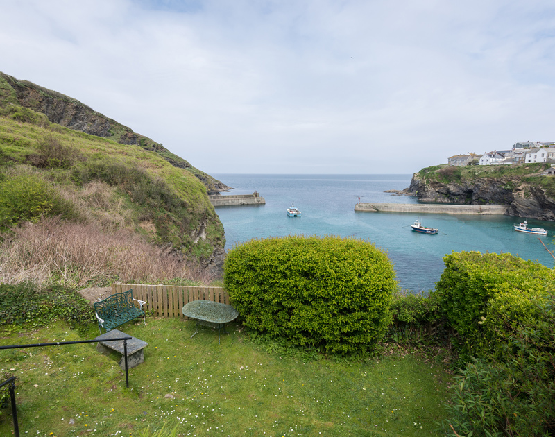 From Northcliffe's garden, spot the fishing boats moving through the breakwater in the harbour of Port Isaac