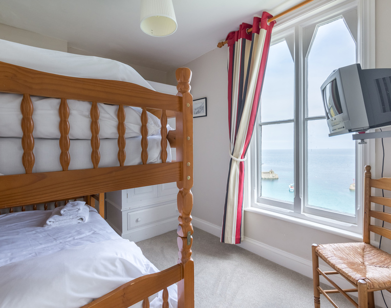 Northcliffe's well furnished bunk room with a large window looking out to the harbour and sea beyond