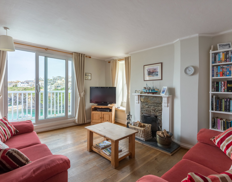 Well furnished, the sitting room at Northcliffe leads on to balcony overlooking Port Isaac's harbour