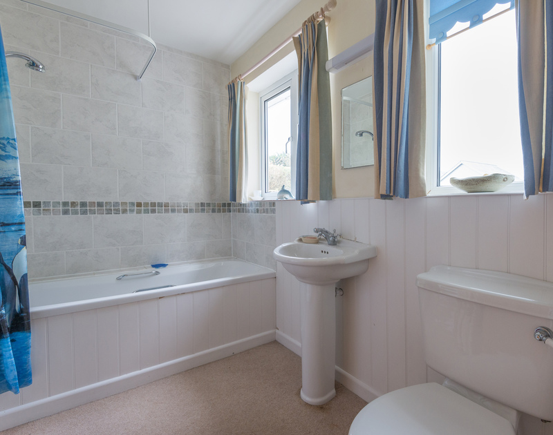 The modern family bathroom with an overhead shower at Pencreek, a traditional self catering holiday cottage in Rock, Cornwall