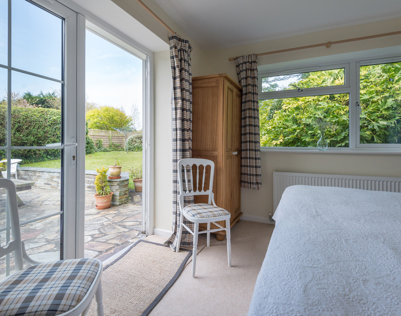 The zip and link bedroom has a gorgeous view and access through patio doors into the garden and patio area for some morning sunshine at Pencreek, a self catering, holiday rental in popular Rock on the North Cornish Coast.