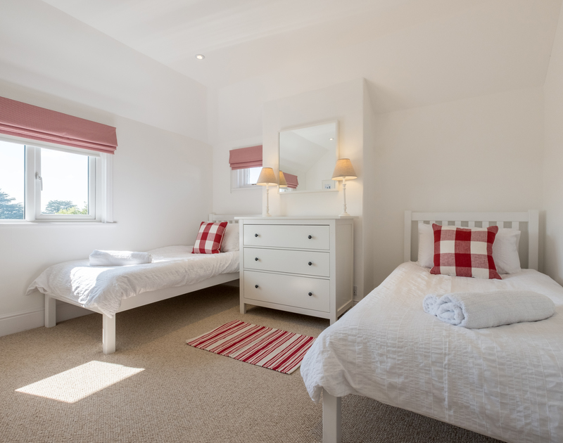 The twin bedroom of The Moorings, a holiday house in Rock, Cornwall, with fresh pops of red soft furnishings.