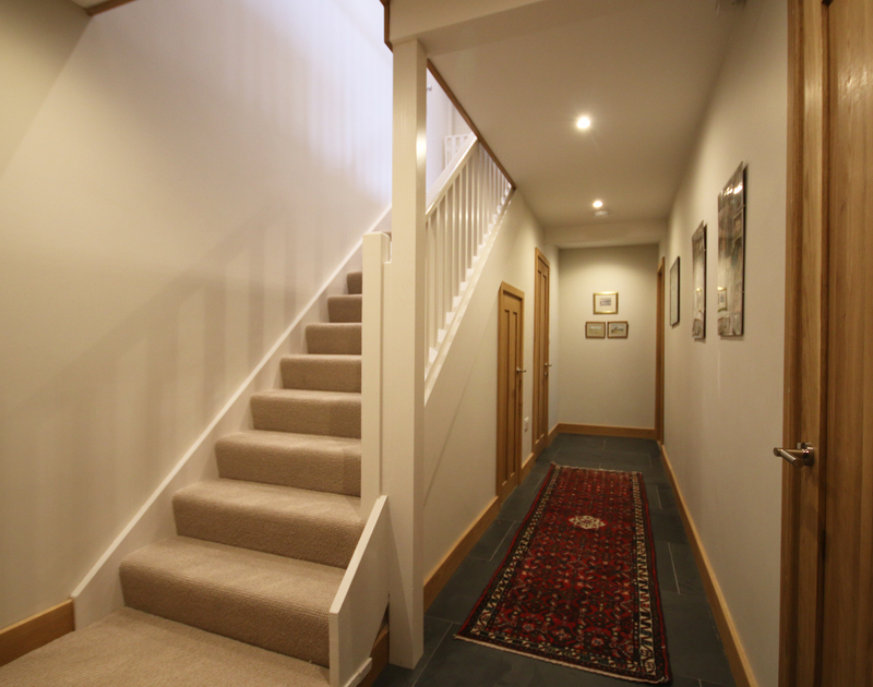 The hallway and stairs up to the first floor living room at Greywings in Rock, Cornwall