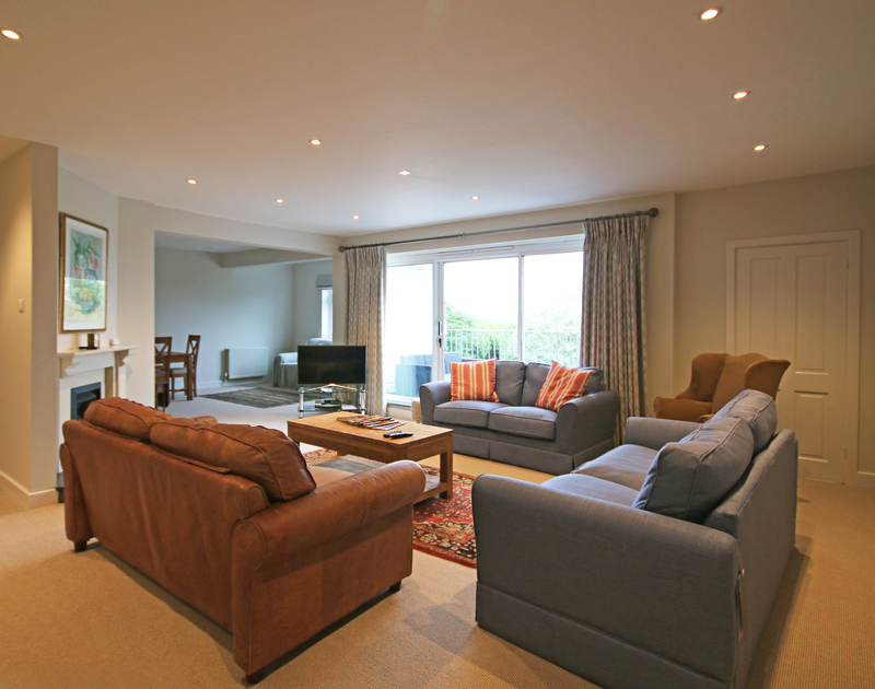 The spacious living room at Greywings in Rock has large patio doors leading onto the balcony offering sea views