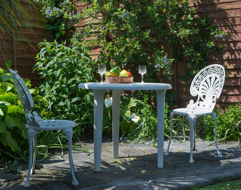 Garden seating for 2 people and a small table in a corner of Caerhayes's garden