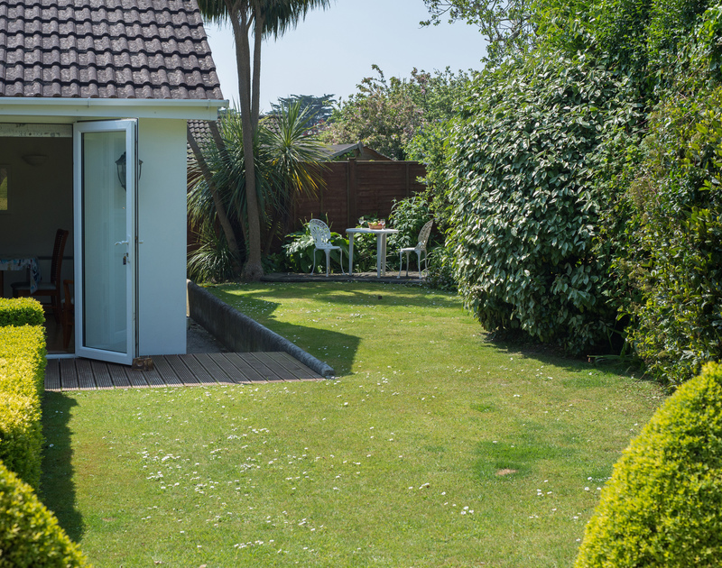 Level lawns and mature planting in the garden of Caerhayes, a holiday house in Rock