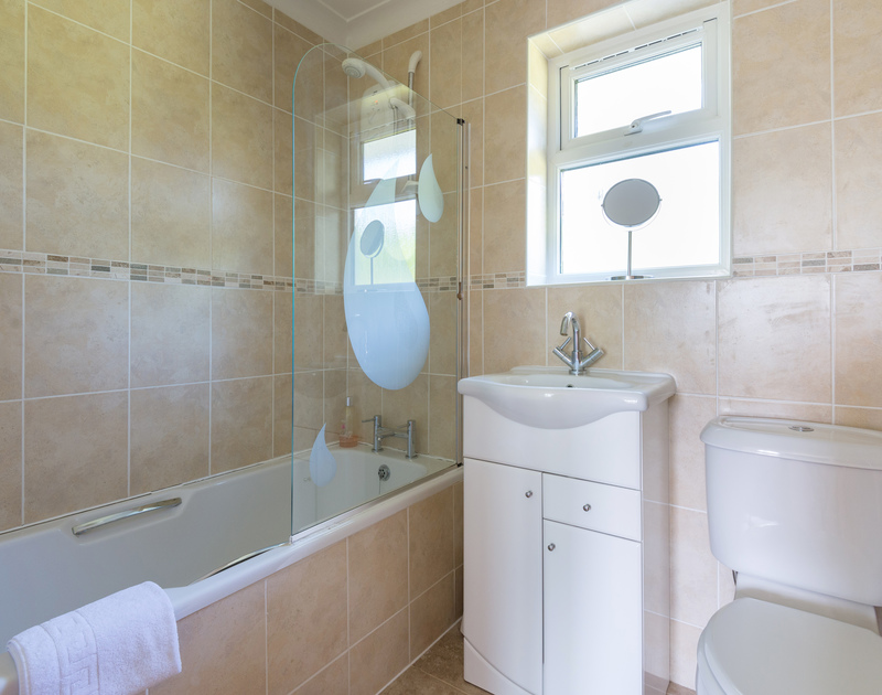 The fully-tiled bathroom of Caerhayes, a self-catering holiday house in Rock, Cornwall