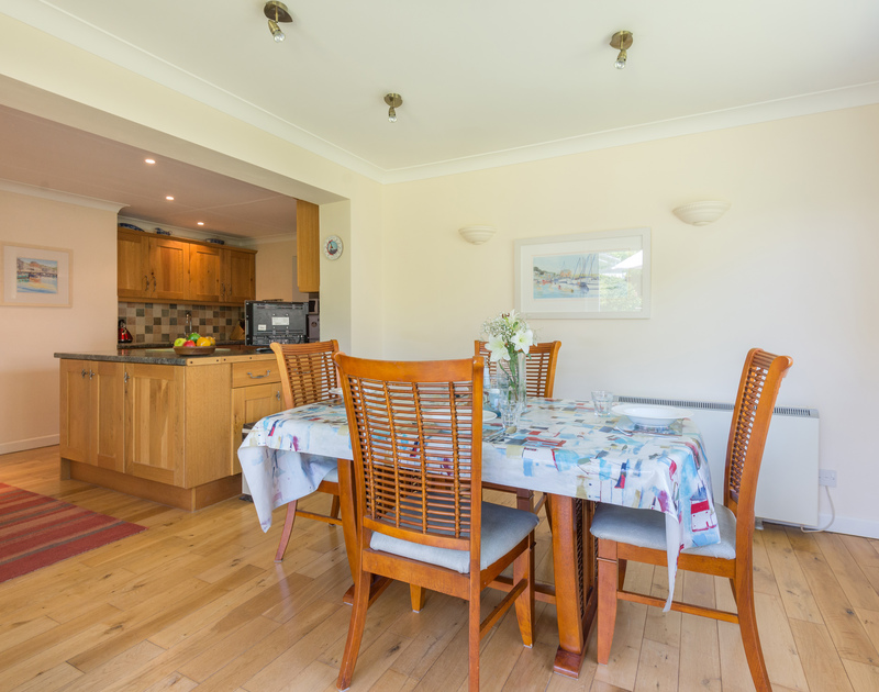 The dining room of Caerhayes, a self-catering holiday house in Rock, Cornwall, with french windows to the garden.