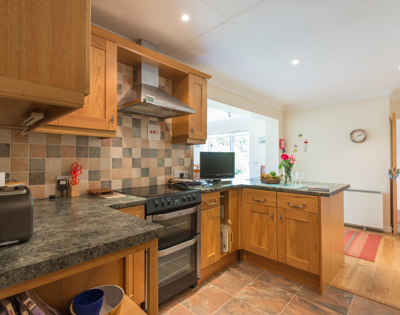 The open-plan, light kitchen with plenty of work surface at Caerhayes